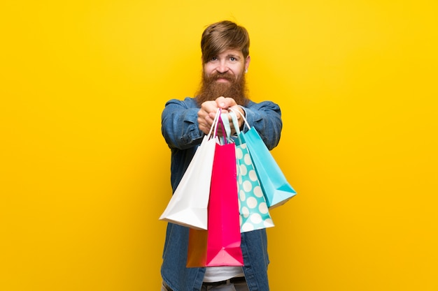 Homem ruivo com barba longa isolado parede amarela segurando um monte de sacolas de compras