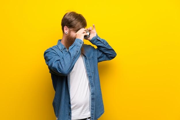 Homem ruivo com barba longa isolado parede amarela segurando uma câmera