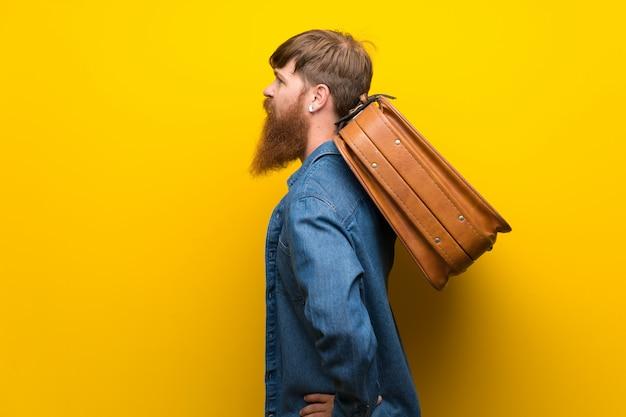Homem ruivo com barba longa isolado parede amarela segurando uma maleta vintage