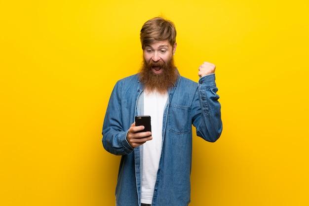 Homem ruivo com barba longa isolado parede amarela usando telefone celular