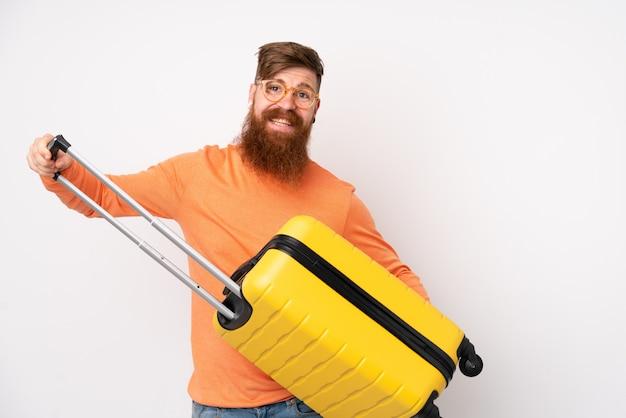 Homem ruivo com barba longa isolado parede branca em férias com mala de viagem