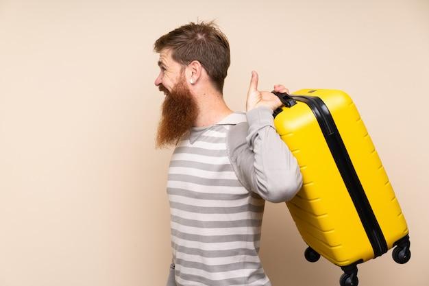 Homem ruivo com barba longa isolado segurando uma mala vintage