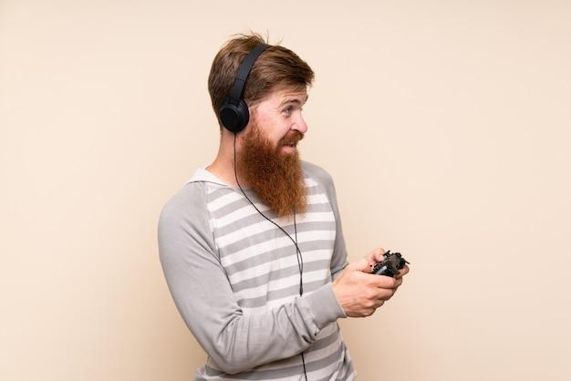 Homem ruivo com barba longa, jogando em videogames