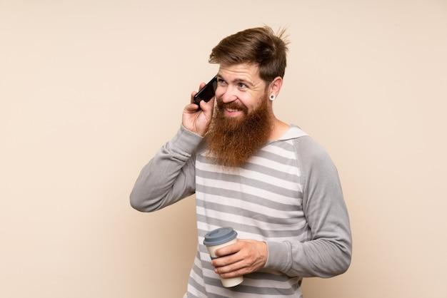 Homem ruivo com barba longa segurando café para tirar e um celular