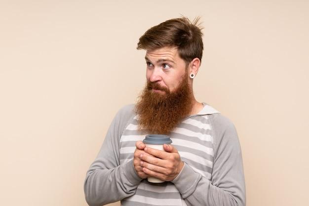 Homem ruivo com barba longa, segurando o café para tirar