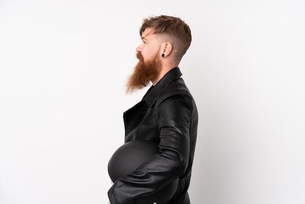 Homem ruivo com barba longa, segurando um capacete de moto sobre parede branca isolada, olhando para o lado