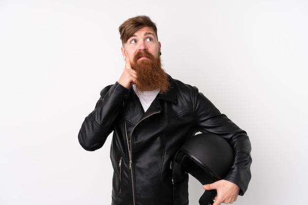 Homem ruivo com barba longa, segurando um capacete de moto sobre parede branca, pensando em uma idéia
