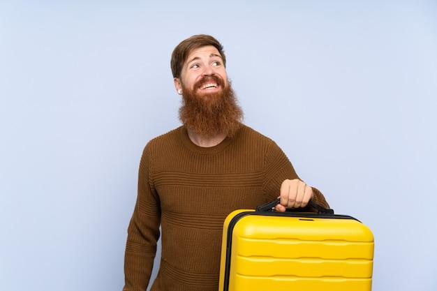Homem ruivo com barba longa, segurando uma mala, olhando para cima enquanto sorrindo