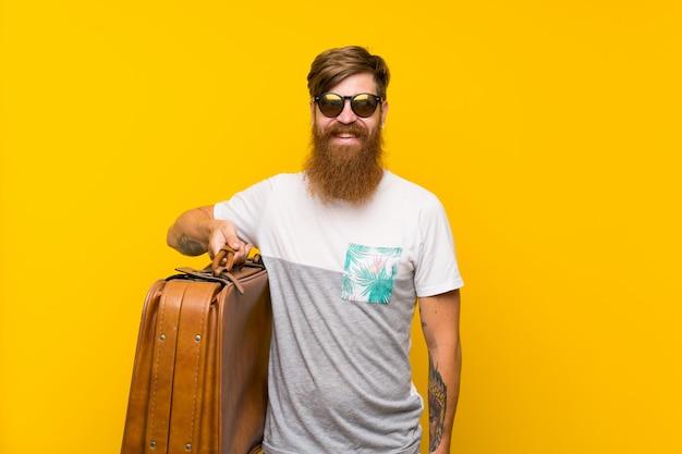 Homem ruivo com barba longa, segurando uma mala vintage sorrindo muito