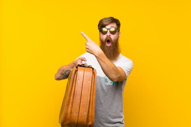 Homem ruivo com barba longa, segurando uma mala vintage surpreso e apontando o lado
