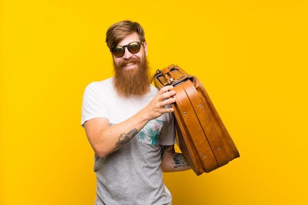 Homem ruivo com barba longa, segurando uma mala vintage
