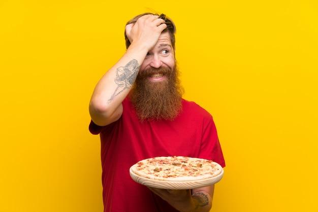 Homem ruivo com barba longa, segurando uma pizza sobre parede amarela isolada percebeu algo