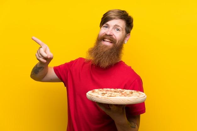 Homem ruivo com barba longa, segurando uma pizza sobre parede amarela isolada surpreendeu e apontando o dedo para o lado