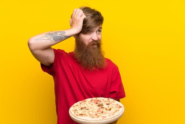 Homem ruivo com barba longa, segurando uma pizza sobre parede amarela isolada, tendo dúvidas e com a expressão do rosto confuso