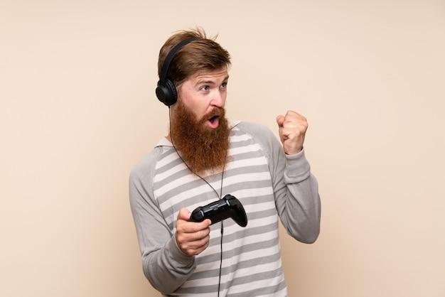Homem ruivo com barba longa, sobre fundo isolado, jogando em videogames