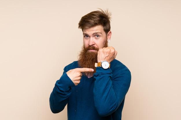 Homem ruivo com barba longa, sobre fundo isolado, mostrando o relógio de mão com expressão séria