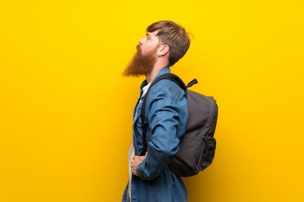 Homem ruivo com barba longa sobre parede amarela isolada com mochila