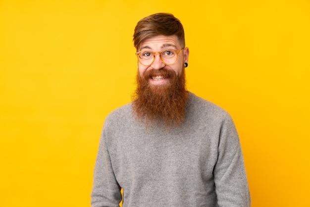 Homem ruivo com barba longa sobre parede amarela isolada com óculos e feliz