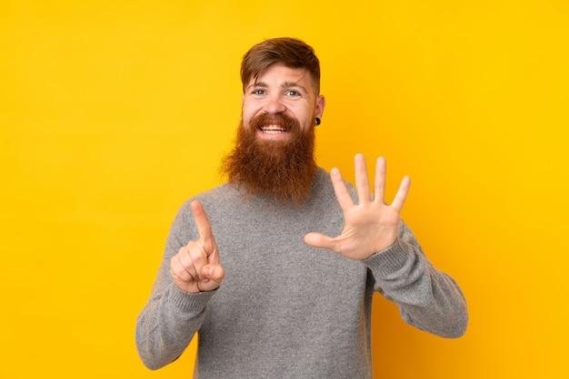 Homem ruivo com barba longa sobre parede amarela isolada, contando seis com os dedos