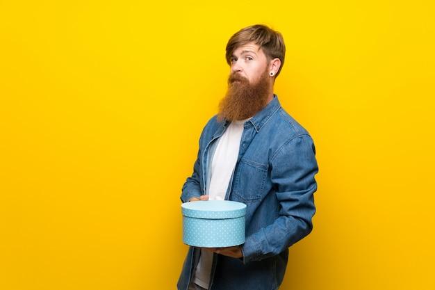 Homem ruivo com barba longa sobre parede amarela isolada, segurando a caixa de presente