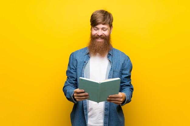 Homem ruivo com barba longa sobre parede amarela isolada segurando e lendo um livro