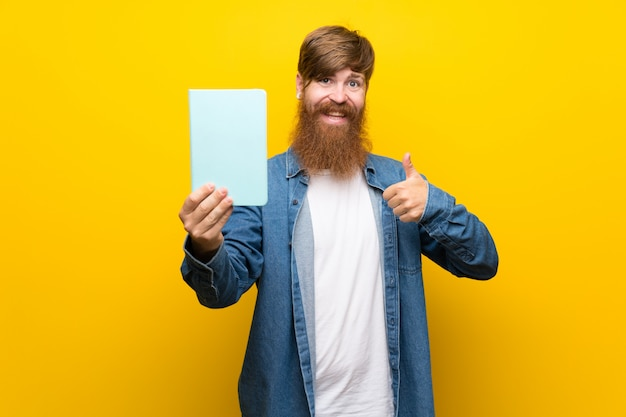 Homem ruivo com barba longa sobre parede amarela isolada, segurando e lendo um livro