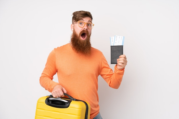 Homem ruivo com barba longa sobre parede branca isolada em férias com mala e passaporte e surpreso