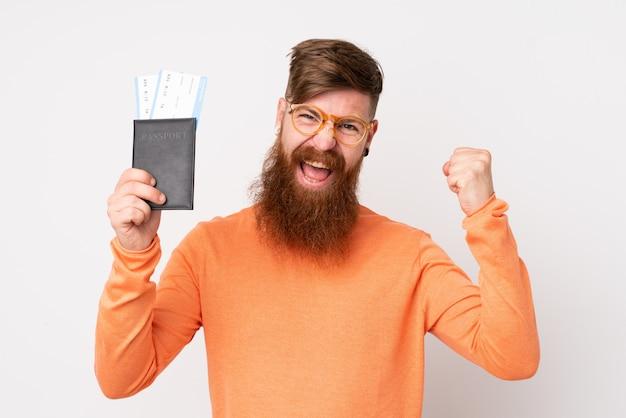 Homem ruivo com barba longa sobre parede branca isolada feliz em férias com bilhetes de avião e passaporte