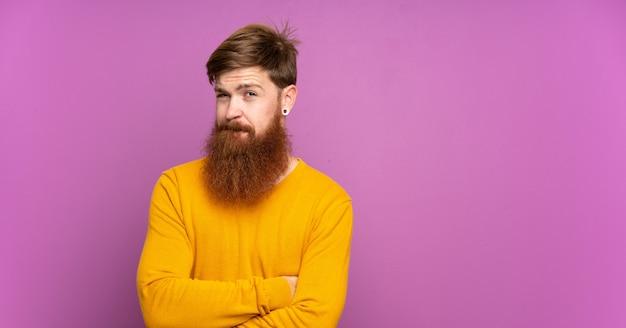 Homem ruivo com barba longa sobre sentimento roxo isolado chateado