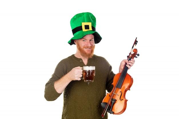 Homem ruivo com chapéu verde e um violino bebendo uma cerveja