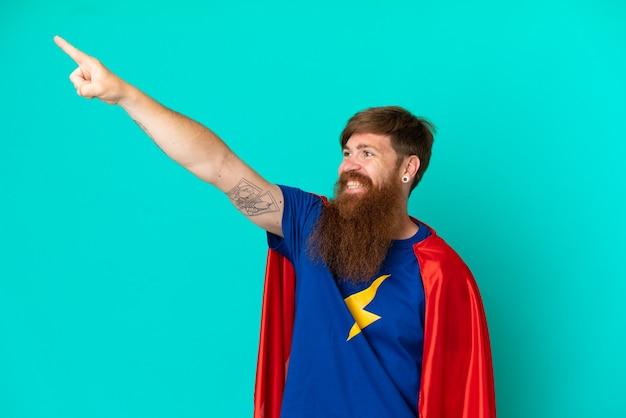Homem ruivo com fantasia de super-herói e gesto orgulhoso