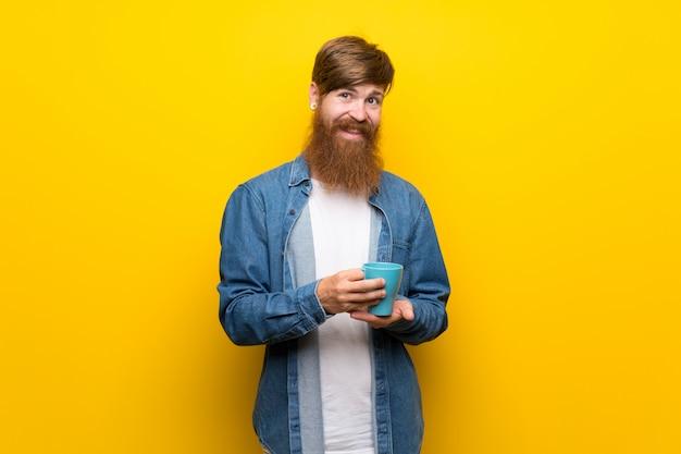 Homem ruivo, com, longo, barba, sobre, isolado, amarela, parede, segurando, xícara quente café