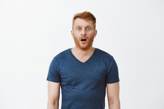 Homem ruivo com o queixo caído ao ver paisagens incríveis e incríveis, posando sobre uma parede cinza em uma camisa azul casual, arfando, olhando emocionado e surpreso sobre a parede cinza