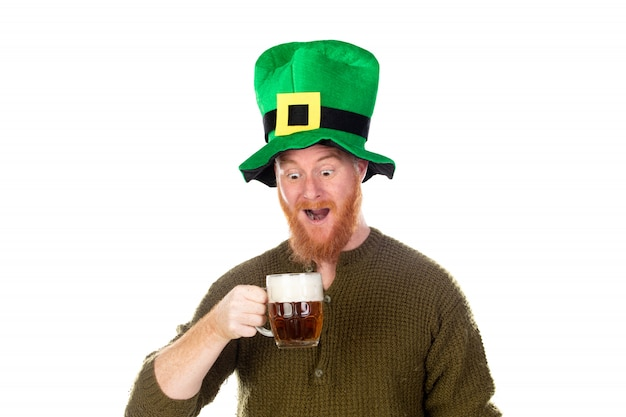 Homem ruivo com um grande chapéu verde, bebendo uma cerveja
