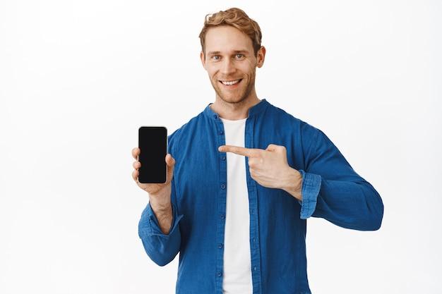 Homem ruivo confiante e sorridente apontando para a tela do telefone e olhando para a frente, recomendando uma boa aplicação no smartphone, exibição de oferta de compra, parede branca