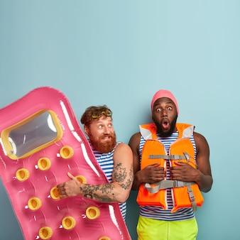 Homem ruivo de barba engraçado segurando colchão inflado, homem de pele escura chocado com medo de nadar