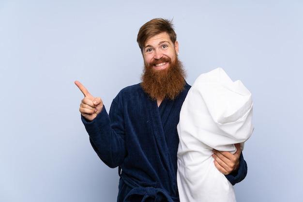 Homem ruivo de pijama, apontando para o lado para apresentar um produto