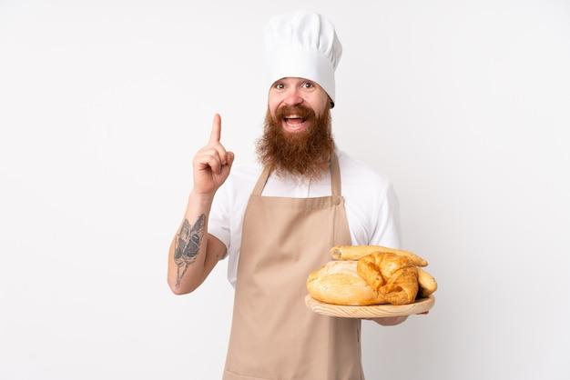 Homem ruivo de uniforme de chef. padeiro masculino segurando uma mesa com vários pães apontando para cima uma ótima idéia