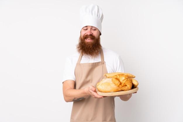 Homem ruivo de uniforme de chef. padeiro masculino segurando uma mesa com vários pães com expressão feliz