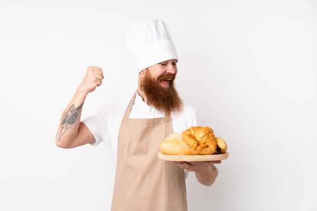 Homem ruivo de uniforme de chef. padeiro masculino segurando uma mesa com vários pães comemorando uma vitória