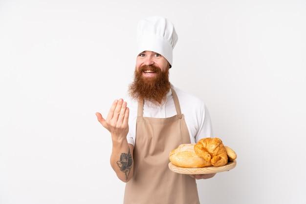 Homem ruivo de uniforme de chef. padeiro masculino segurando uma mesa com vários pães, convidando para vir com a mão.