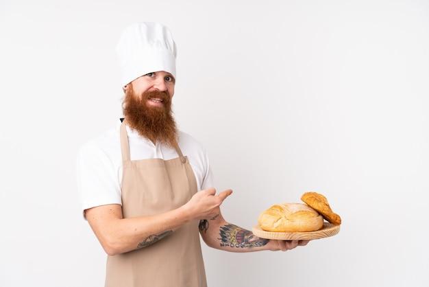 Homem ruivo de uniforme de chef. padeiro masculino segurando uma mesa com vários pães e apontando