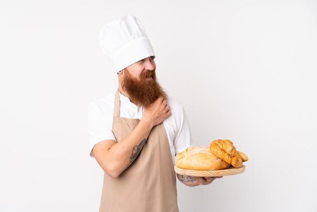 Homem ruivo de uniforme de chef. padeiro masculino segurando uma mesa com vários pães, pensando uma idéia e olhando de lado