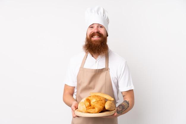 Homem ruivo de uniforme de chef. padeiro masculino segurando uma mesa com vários pães, sorrindo muito