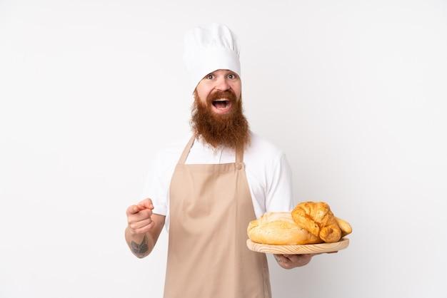 Homem ruivo de uniforme de chef. padeiro masculino segurando uma mesa com vários pães surpreso e apontando o dedo para o lado