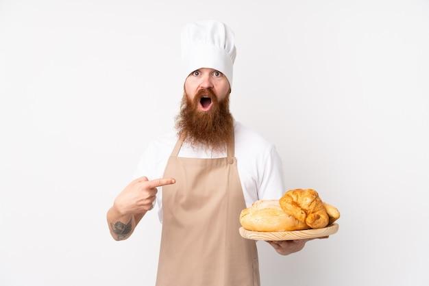 Homem ruivo de uniforme de chef. padeiro masculino segurando uma mesa com vários pães surpreso e apontando o lado