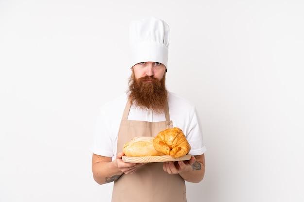 Homem ruivo de uniforme de chef. padeiro masculino segurando uma mesa com vários pães