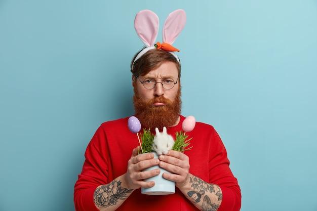 Homem ruivo descontente sorri e parece infeliz, estragou o dia, posa com pequeno coelhinho da páscoa, ovos coloridos decorados, usa óculos redondos, orelhas de coelho, posa com expressão sombria