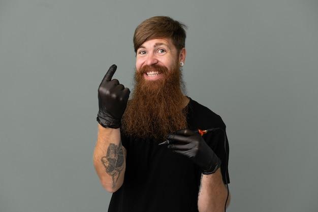 Homem ruivo do tatuador isolado em um fundo azul fazendo gesto de aproximação