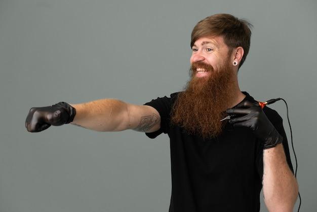 Homem ruivo do tatuador isolado em um fundo azul fazendo um gesto de polegar para cima